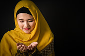 Portrait of beautiful young muslim woman on a black background.