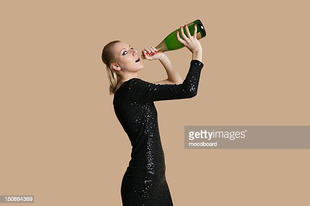 Portrait of beautiful young woman drinking champagne from bottle over colored background
