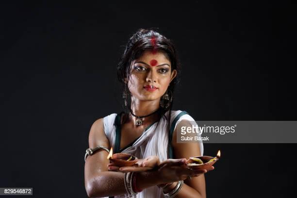Portrait of beautiful  young woman holding diya