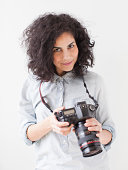 Portrait of beautiful young woman holding professional camera