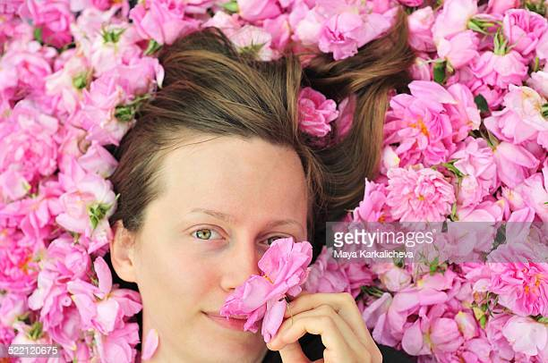 Portrait of beautiful young woman in bed of roses