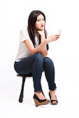 Portrait of beautiful young woman in casuals sitting on stool with mobile phone against white background