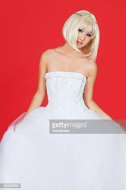 Portrait of beautiful young woman in wedding dress standing against red background