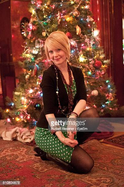 Portrait of beautiful young woman kneeling against decorated Christmas tree