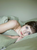 Portrait of beautiful young woman lying in bed wrapped in duvet