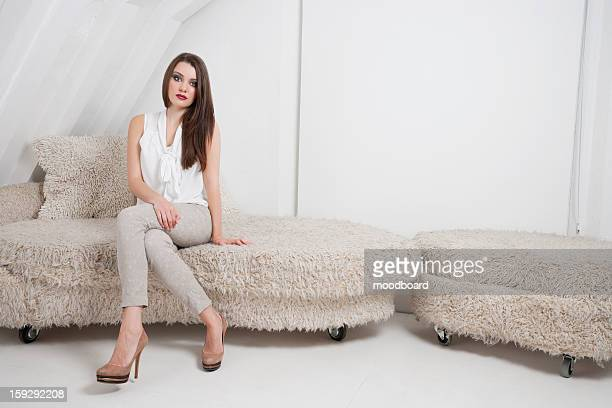 Portrait of beautiful young woman sitting on sofa