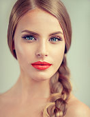 Close up portrait of beautiful young woman with braid(pigtail), bright red lips and blue eyes. Fashion ,beauty and cosmetic.