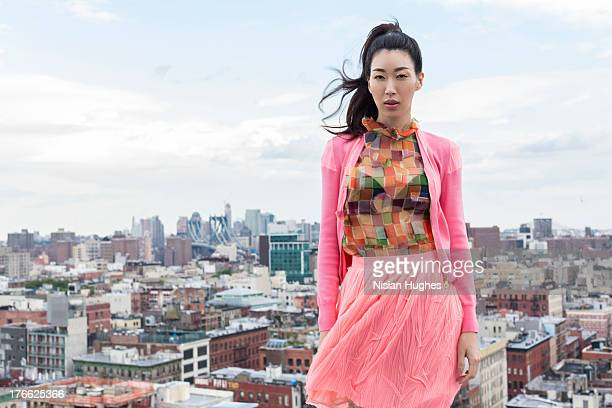 portrait of beautiful young woman with city behind