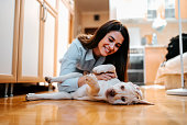 Portrait of beautiful young woman with dog playing at home.