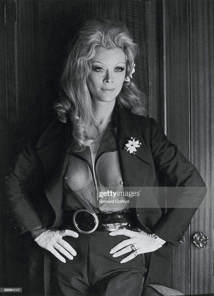Portrait of Belgian actress Monique Van Vooren as she poses with her hands on her hips, dressed in a transparent shirt under her opne jacket, 1970s.