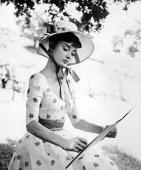 Portrait of Belgianborn American actress Audrey Hepburn as she wears a bonnet and sketches on the set of 'War and Peace' directed by King Vidor 1956