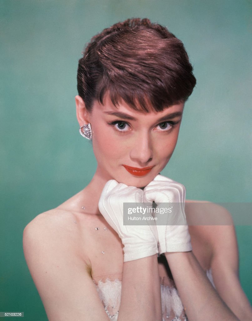 Portrait of Belgian-born American actress <a gi-track='captionPersonalityLinkClicked' href=/galleries/search?phrase=Audrey+Hepburn&family=editorial&specificpeople=86470 ng-click='$event.stopPropagation()'>Audrey Hepburn</a> (1929 - 1993) as she wears a strapless gown and holds white kid-gloved hands up to her chin, early 1950s.