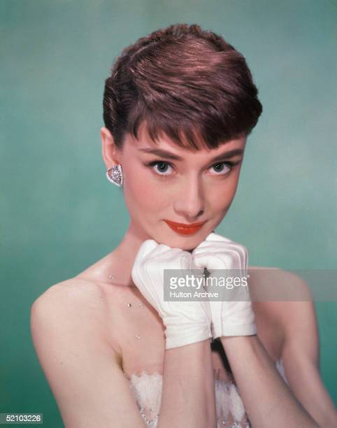 Portrait of Belgianborn American actress Audrey Hepburn as she wears a strapless gown and holds white kidgloved hands up to her chin early 1950s