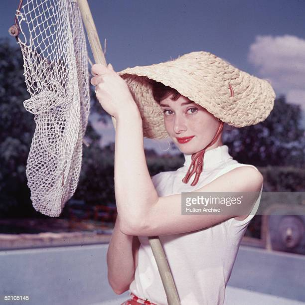 Portrait of Belgianborn American actress Audrey Hepburn as she wears a peculiar hat and sleeveless blouse and holds a pool cleaning net beside a dry...