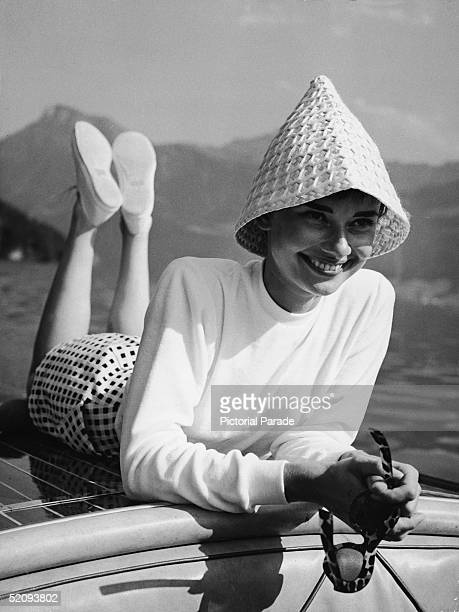 Portrait of Belgianborn American actress Audrey Hepburn wears a peculiar hat and lies on the back of a motorboat on a lake in Switzerland early 1950s