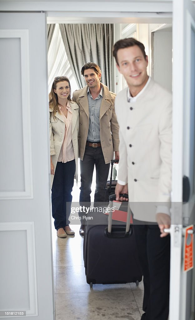 Portrait of bellman opening hotel room door with couple in background : Foto de stock