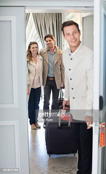 Portrait of bellman opening hotel room door with couple in background