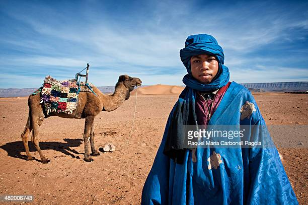 Portrait of Berber boy with his camel in Tinfou dunes near Tamegrout