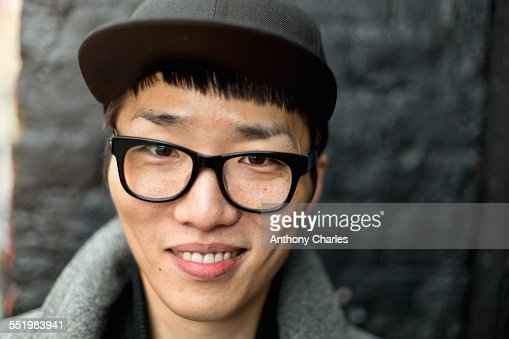 Portrait of bespectacled young man with cap