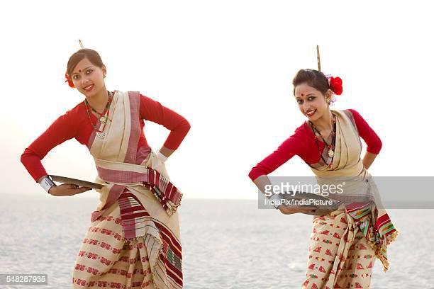 Portrait of Bihu women dancing with brass plates