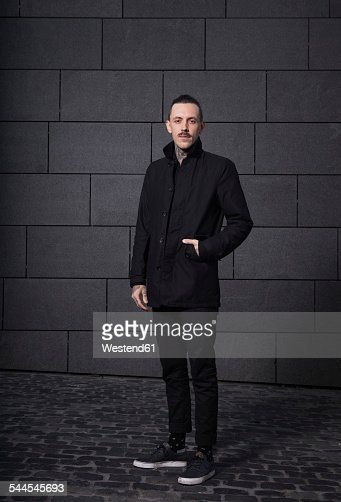 Portrait of black dressed man in front of grey background