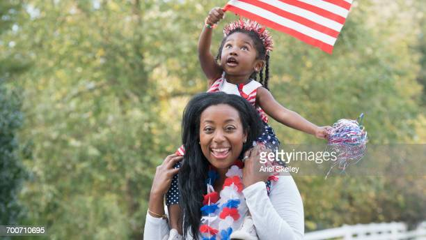 Portrait of Black mother and daughter celebrating 4th of July in park