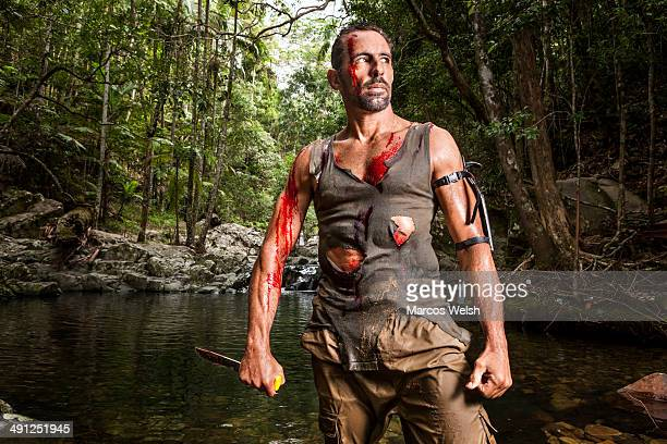 Portrait of bleeding man with knife in the jungle