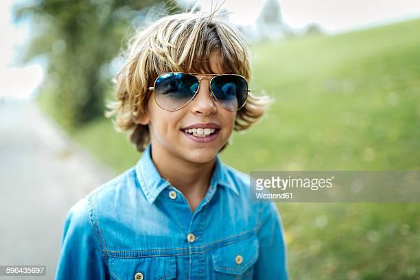Portrait of blond boy wearing blue coloured sunglasses and denim shirt