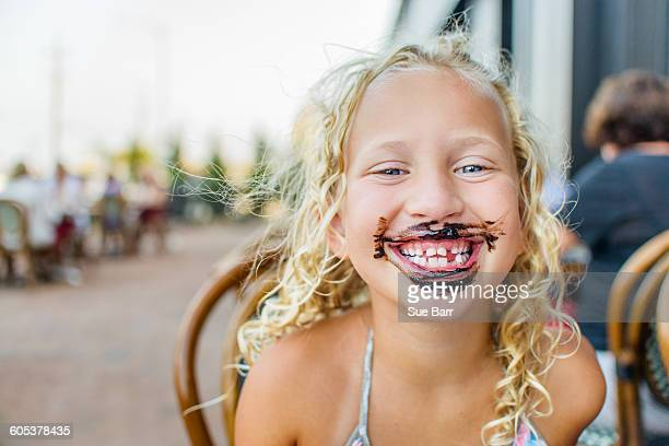 Portrait of blond haired girl at sidewalk cafe with sauce covered mouth