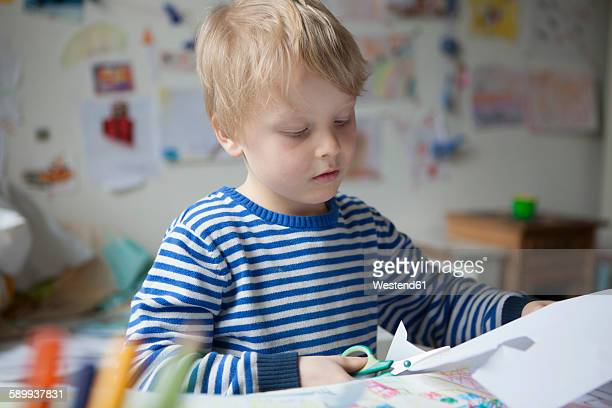 Portrait of blond little boy tinkering