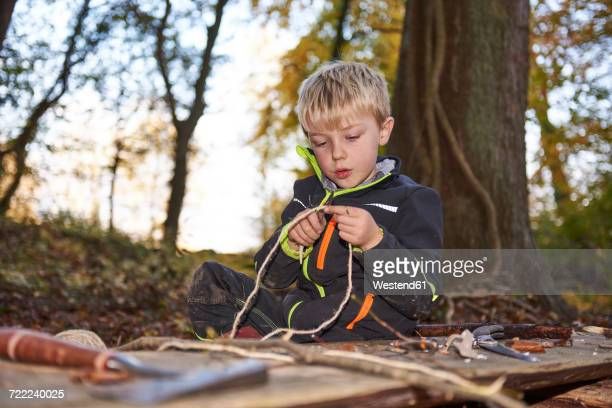Portrait of blond little boycutting rope with knife outdoors