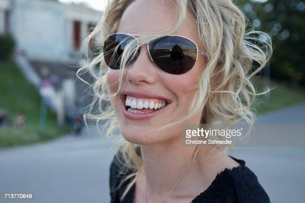 Portrait of blond mid adult woman wearing sunglasses in park