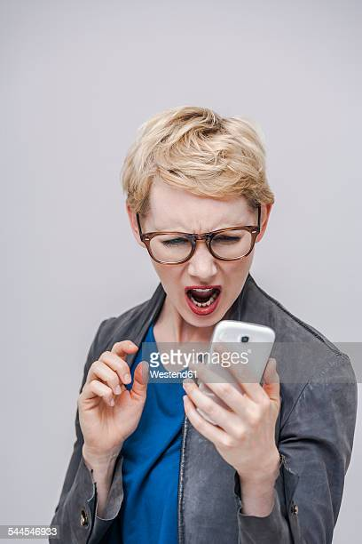 Portrait of blond woman looking at her smartphone screaming