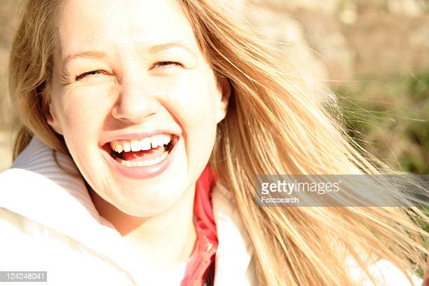 Portrait of blond woman smiling, blinded by the sunlight