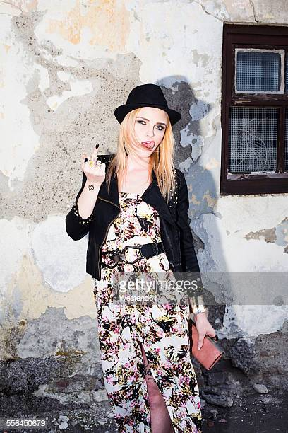 Portrait of blond woman sticking out tongue and giving the finger