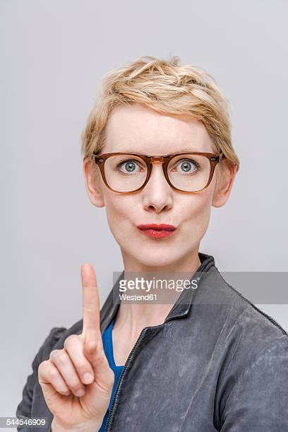 Portrait of blond woman wagging forefinger