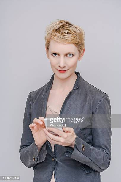 Portrait of blond woman with her smartphone in front of grey background