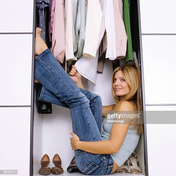 portrait of blonde young woman crouched in wardrobe