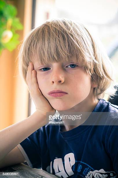 Portrait of bored little boy with head in his hand