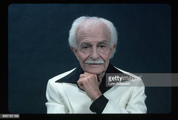 1979 Portrait of Boston Pops Orchestra Arthur Fiedler He is dressed in a white suit and a black wide collar shirt His hand is placed on his chin and...