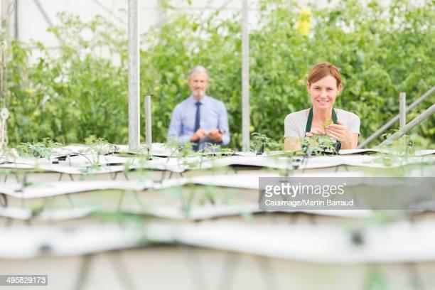 Portrait of botanists examining plants in greenhouse