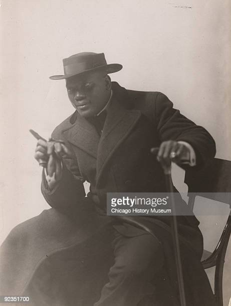 Portrait of boxing champ Jack Johnson dressed formally in hat and overcoat seated and leaning on a walking stick Chicago IL ca1912