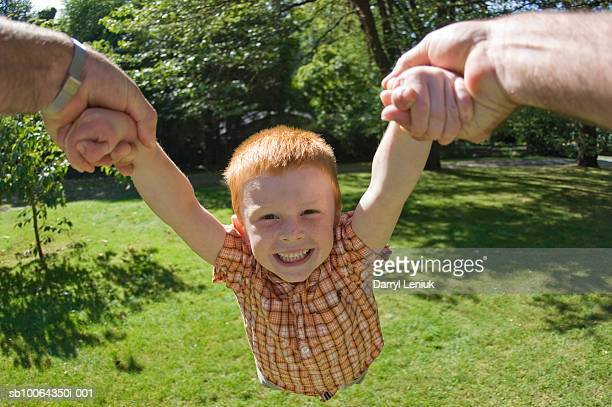 Portrait of boy (3-5) being twirled in mid air by father (close-up of hands)