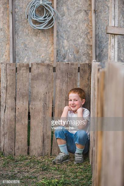 Portrait of boy crouching against wooden planks in park
