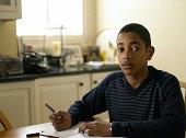 Portrait of boy (12-13) doing homework at kitchen table, portrait