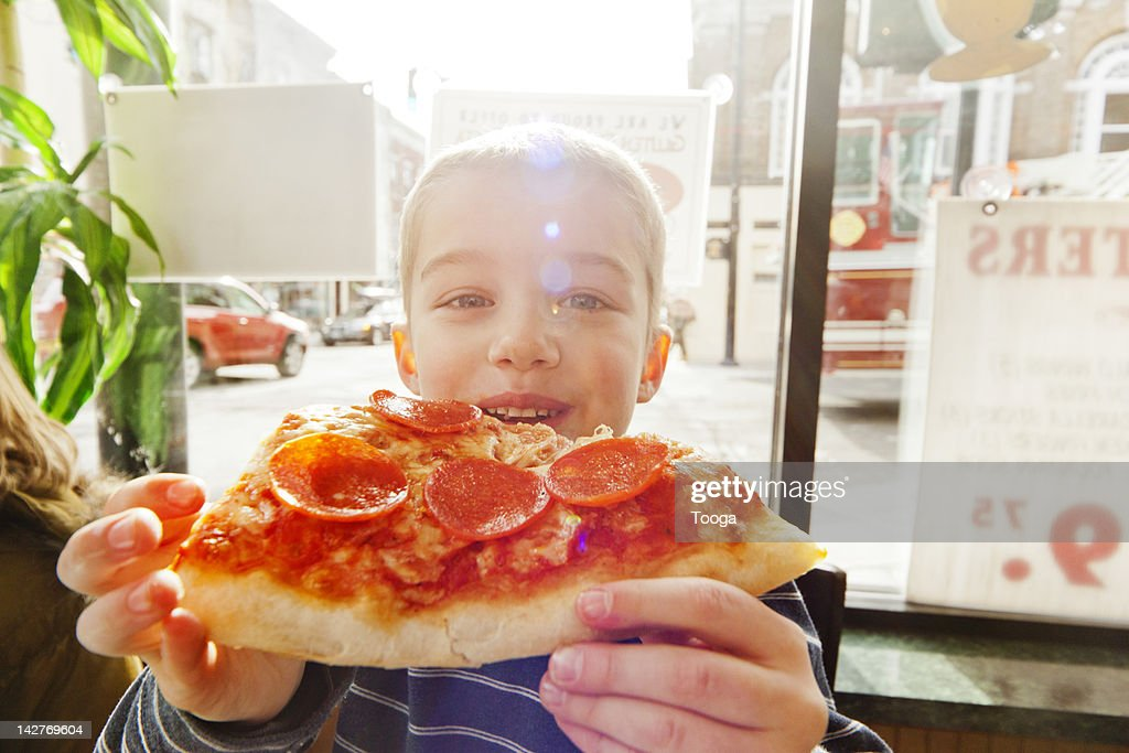 Portrait of boy eating slice of pizza : Stock Photo