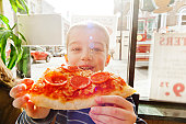 Portrait of boy eating slice of pizza