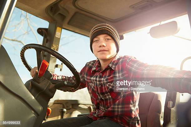Portrait of boy farmer driving tractor on dairy farm
