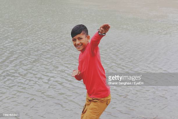 Portrait Of Boy Gesturing While Standing In Lake