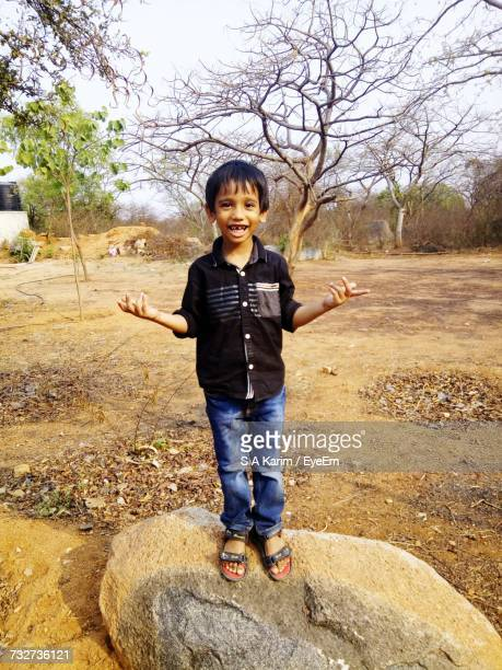 Portrait Of Boy Gesturing While Standing On Rock